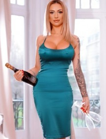 Emelda in a sexy green dress holding champagne