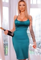 Emelda in a sexy green dress holding a bottle of champagne