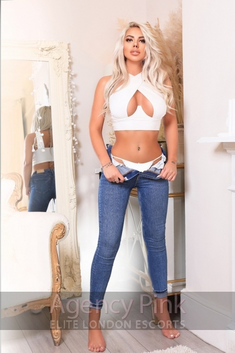 A picture of escort Amira standing by the mirror with her jeans pulled down Picture 5